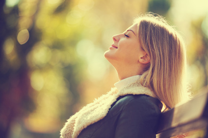 Young happy woman enjoying fresh air in autumn, intentionally toned.